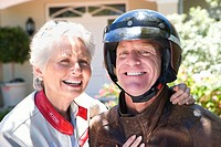 Senior couple standing and sitting in driveway, senior man wearing motorbike crash helmet, smiling, close-up, portrait