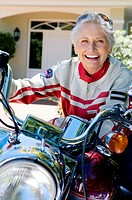 Senior woman sitting on motorbike on driveway, smiling, close-up, front view, portrait