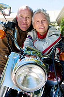 Senior couple sitting on motorbike on driveway, smiling, front view, close-up, portrait