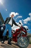 Senior man standing beside motorbike on driveway, holding crash helmet, smiling, portrait surface level, tilt, lens flare