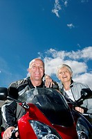 Senior couple posing beside red motorbike on driveway, woman leaning on manÔÇÖs shoulder, smiling, front view, low angle view, portrait