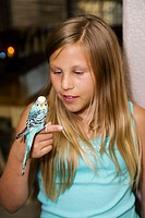 Young girl holds and looks at a blue parakeet