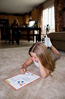 young girl does her homework on floor, mother in background