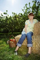 Woman sitting on hay bales near orchard portrait (thumbnail)