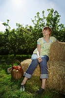 Woman sitting on hay bales near orchard (thumbnail)