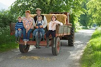 Parents with three children 5-9 sitting on trailer on country lane portrait (thumbnail)