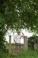 Man standing at gate in countryside