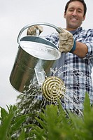 Man watering crops in field (thumbnail)