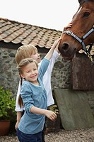 Sister and brother 5_6 7_9 stroking horse outside stable