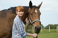 Woman with horse in field portrait