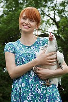 Woman holding hen in garden portrait