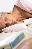 Woman in her 20's sleeping restfully with alarm close by