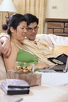 Asian couple in their 30´s watching movie on laptop together happily