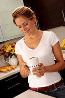 Woman In Kitchen Drinking Cappuccino / Latte Coffee