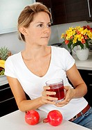 Woman In Kitchen With Glass Of Pomegranate Juice