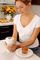 Woman In Kitchen Drinking Cappuccino With Muffin