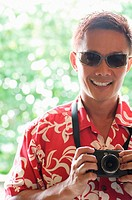 Man in floral shirt and sunglasses holding a camera