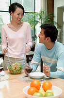 Man sitting at dining table, woman standing next to him tossing a salad