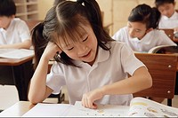 Boys and girls studying in classroom, focus on girl in front