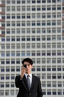 Businessman looking through camera phone