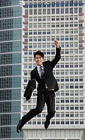Businessman jumping in air, smiling