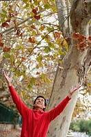 Man standing beneath a tree, arms outstretched