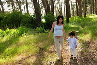Mother and son walking on path in woods