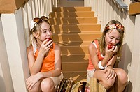 Twin girls eating apples