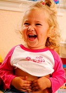 Close-up of a girl touching her belly button and laughing