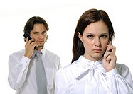 Portrait of a businessman and a businesswoman using mobile phones