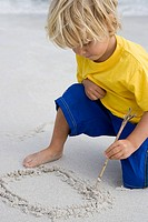 Boy drawing in the sand