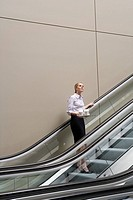 Businesswoman standing on escalator