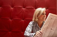 Businesswoman working at a table with red seating (thumbnail)