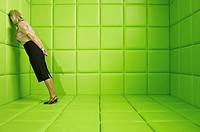 Woman leaning head against wall in a green padded cell
