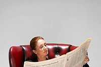 Businesswoman in a comfy leather chair with newspaper (thumbnail)