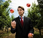 Man Juggling apples in orchard