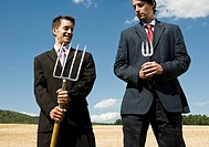 Two men holding garden tools next to each other