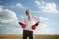 Businesswoman in wheat field wearing boxing gloves