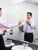 Man practicing speech in office washroom mirror