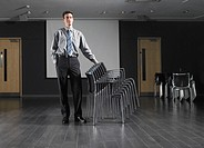 Man standing with stack of chairs in empty presentation room