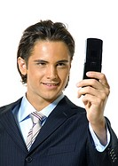 Close-up of a businessman text messaging with a mobile phone and smiling