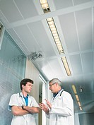 Mature doctor and young doctor in discussion in a lobby of a hospital low angle
