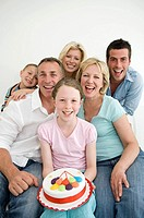 Girl holding a birthday cake surrounded by family