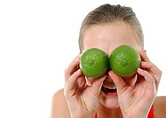 Close-up of a young woman holding two limes in front of her eyes