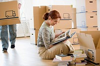 Woman looking through books as she packs