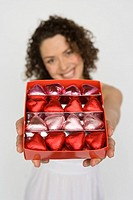 Woman holding out box of chocolates