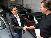 Two men shaking hands in front of sports car