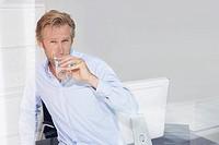 Man in office drinking water with reflections