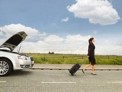Businesswoman Walking Away from Broken Down Car