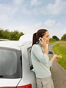 Woman Talking on Cell Phone Leaning Against Broken Down Car